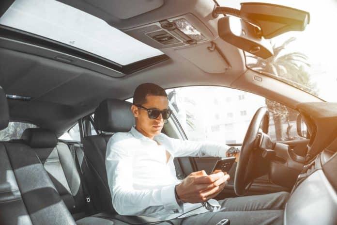Mand i hvid trøje kigger på telefon i bil