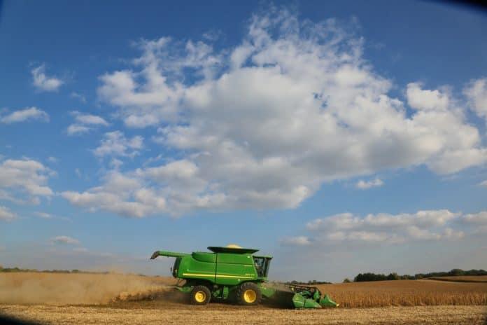 Mejetærsker kører på en mark med blå himmel
